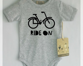Cute baby bodysuit with bicycle print. Ride on baby clothes. Modern baby clothes.