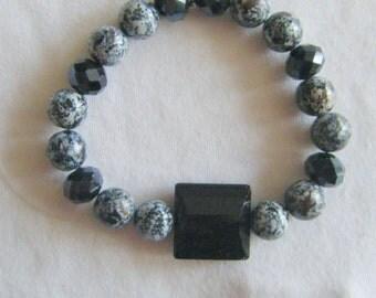 Unisphere...a stretch bracelet.  Black/white speckled beads with black glass beads.