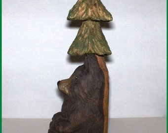 HANDCARVED BLACK BEAR Resting on the Trunk of a Pine Tree. This lazy bear is taking an afternoon nap leaning back onto a pine tree.