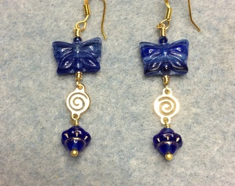 Dark blue Czech glass butterfly bead dangle earrings adorned with gold swirly connectors and dark blue Saturn beads.