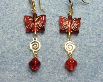 Cranberry red butterfly bead dangle earrings adorned with gold swirly connectors and red Saturn beads.