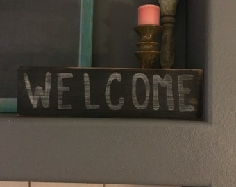 "Wood sign ""welcome"" black with white writing"