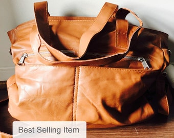 Large,soft genuine leather handbag. Lots of compartments, flat handles and long straps makes a great leather shoulder travel tote bag.