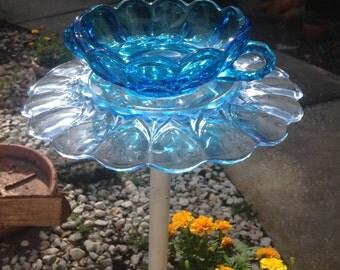 Blue glass flower garden art with vintage plates