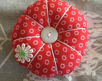 Pin cushion in red ditsy daisy fabric with daisy appliqué and buttons. A lovely gift for a friend of a Christmas stocking filler
