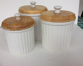 Stylish vintage French style white ceramic canister set with wooden lids. White fluted canisters Preferred stock 3 piece white canister set.