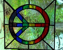 Multicolored stained glass peace sign on iridescent clear glass sun-catcher.