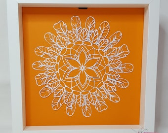 Mandala catcher dreams directed by papercut or kirigami handmade on orange plain background