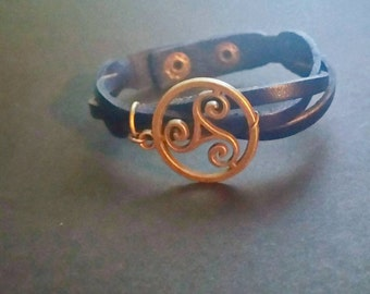 Antigue gold tone Triskelion charm on a dark blue faux leather cuff
