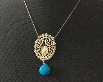 A silver pendant with a drop of gemstone.