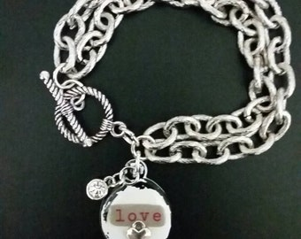 Double strand silver chunky link chain bracelet with love resin charm and rhinestone accent, togle closure. Valentine's Day