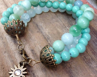 Multistrand colorful blue beaded charm bracelet with antique gold small mirrored sun charm