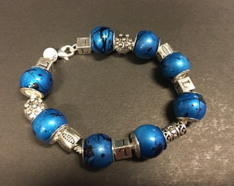 Sterling Silver Bracelet with blue and black glass beads and varied silver spacers.