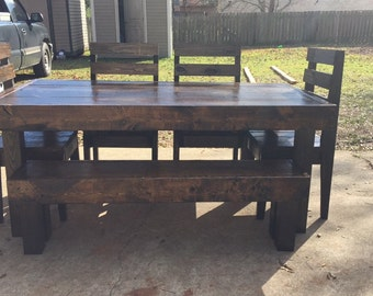 Bulky farmhouse table with bench and chairs .
