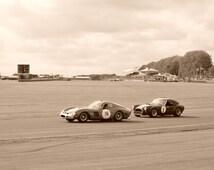 Wall art: Framed photograph of a Ferrari chased by an AC cobra - 30x40cm - Cepia - black frame