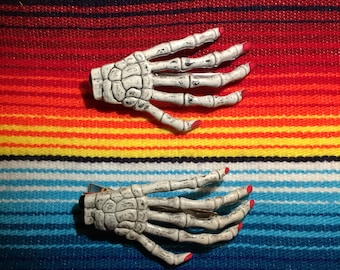 One pair of skeleton hands hair clips with red nail varnish