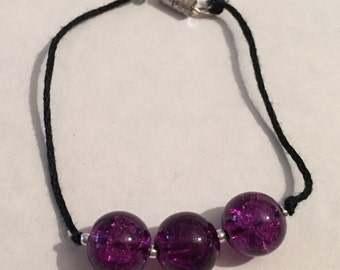 Three large purple beads on a black string bracelet with screw clasp