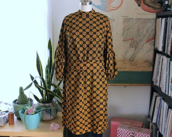 mod 60s belted dress with medallion print . black and gold womens 1960s dress with balloon sleeves . womens medium large