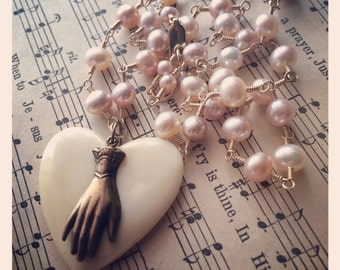 Comfort . Natural peach & mauve freshwater pearls with vintage carved bone heart and brass hand .