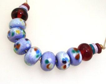 Handmade Lampwork Glass Beads - Milan! 9 bead set. Color splashed white enamel on lavender, dark amber accent beads.