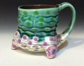 Copper green wavy mug with feet on white with light yellow bottom -modern fun quality pottery handmade in Minnesota