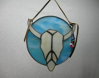 Stained glass cow skull overlaid on circle