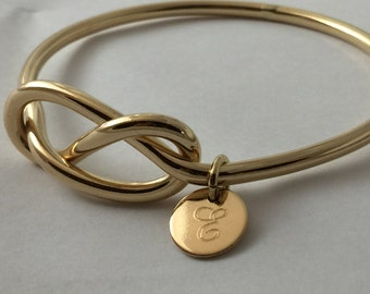 Chunky gold infinity knot bangle with personalized disc charm, 8 gauge thick statement bracelet
