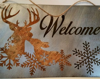 "Rusty deer and snowflake Welcome 8""x12"" etched metal sign in silver, rust, and dark brown"