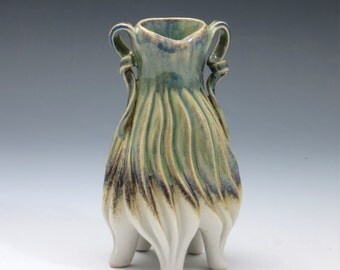 Porcelain lady vase in green, purple, tan & white with grooves and handles, hand carved