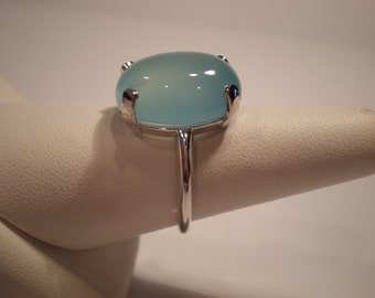 Soothing and beautifully polished aquamarine blue chalcedony oval cabochon set in solid 14K white gold ring