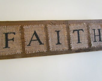"""Old Barn Wood Wall Hanging That Says """"Faith"""" In Black Font Written Neatly On Burlap Squares"""