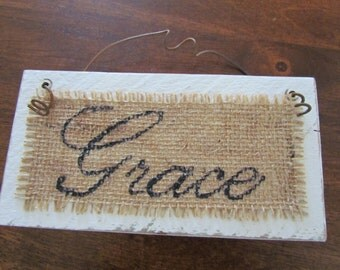 """Small, White Distressed Wood Sign With The Word """"Grace"""" Neatly Written in a Cursive Font in Black on Burlap with Rusty Metal Hanger"""