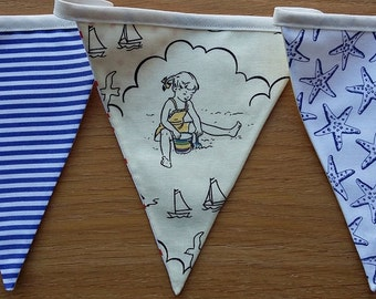Seaside bunting with starfish, stripes and children playing in blue, white and cream fabric with 9 flags