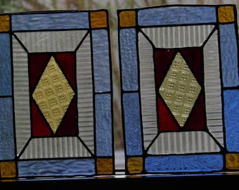 two antique colourful stained glasses blue, red and yellow