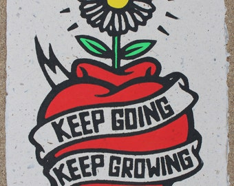New Edition: Keep Going Keep Growing - a linocut of a heart, banner and daisy, hand painted on indian handmade banana paper