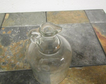 antique Clear Glass  Jug with pour spout and finger handle  with a pattern around it. .