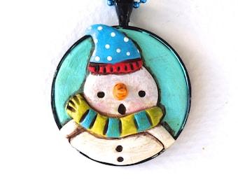 Original Snowman Folk Art Necklace with Sky Blue Hat in Round Black Bezel setting