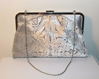A silver kisslock clutch bag in an embossed iridescent velvet celtic design