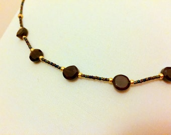 A black beaded necklace with faceted garnets