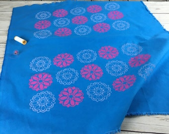 Blue heavyweight cotton fabric, hand printed in pink and lilac with retro 60's ellipse flower design, hand dyed and hand printed for sewing