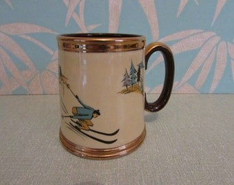 Collectable 1950s Gibsons china tankard with copper gilt edging and winter skier motif