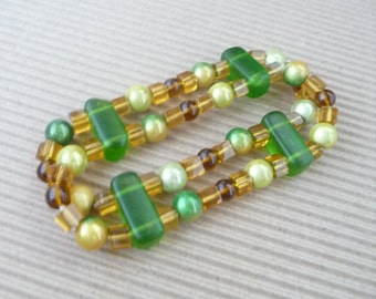 Elastic bracelet with ochre and green glass beads