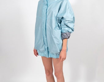 Light blue oversize raincoat fastened with snaps
