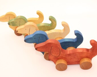 Wooden toy dog on wheels. Wood toys. Animals.
