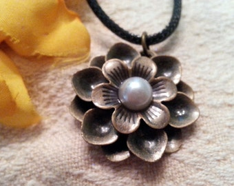 Goldish flower with pearly center pendant on a black cord necklace