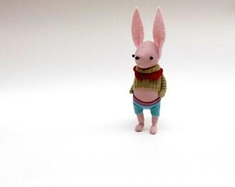 Pink Muslin Rabbit  -  Handmade plush bunny wearing turquoise felt pants and a green woollen pullover.
