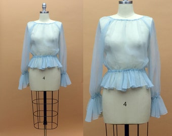 1960s. chiffon baby blue sheer blouse with flounce ruffle sleeves. size small