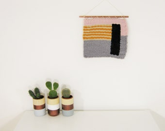Small handwoven wall hanging hangs by a cooper rod