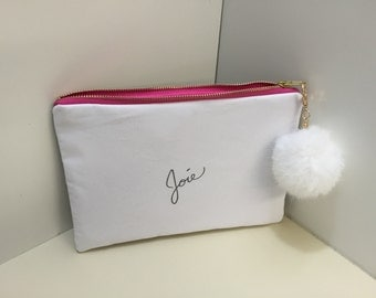 Designer clutch or makeup bag with pink silk lining and beige studs on back