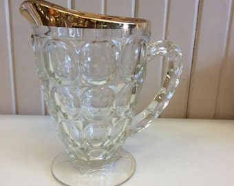 Glass pitcher with gold trim on top
